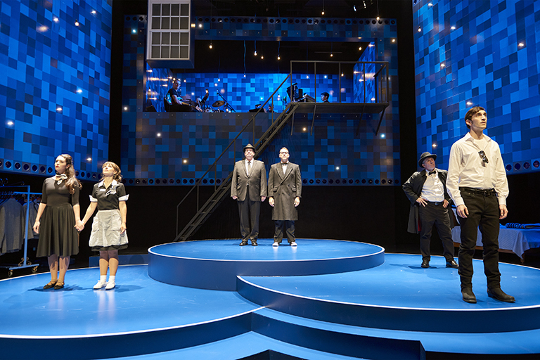 Production still of Fly by Night. Six actors stand scattered on a blue-themed stage. They gaze up at the audience. Above them hang dozens and dozens of lightbulbs, emulating stars.