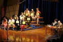 (At desk) Lisa Howard and Greg Stuhr with cast and spellers, including (from bottom r Photo