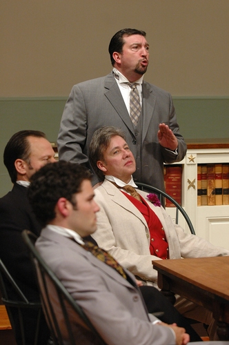 Edward Clarke (standing rear, Joe Henderson) as Edward Carson defends Oscar Wilde (center seated, JM Richardson) during trial one while (l-r) Lord Alfred Douglas (Ara Boghigian) and Edward Carson (Michael Zola) listen.