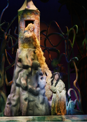 The Witch (Lisa Estridge) climbs up Rapunzel's (Anne Eisendrath) hair