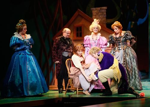 Cinderella's stepsister Florinda (Krista Severeid), her father (Allen Galli), stepsister Lucinda (Darla Cardwell) and Stepmother (Carol Swarbrick) look on as Cinderella (Billie Wildrick) tries on the golden slipper found by her Price (Michael Hunsaker)