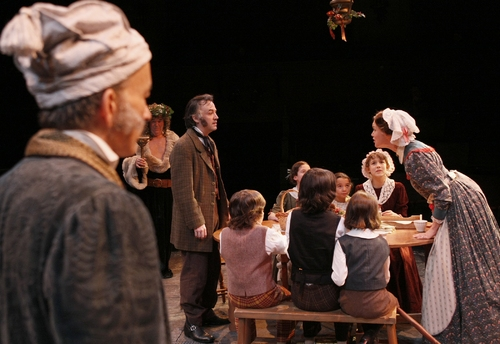 David Pichette as Scrooge, Richard Ziman as Spirit #2 and the cast as the Cratchits Photo