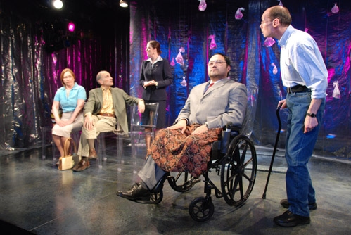 Orville Mendoza (in wheelchair) and John Daggett (standing) as Doug; background, l-r: Dale Soules as Monique, Edward Hajj as Pierre and Mercedes Herrero as Ambassador