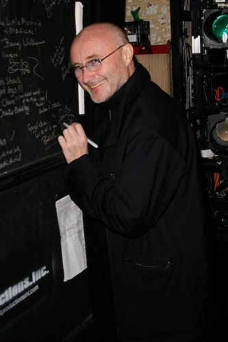 Phil Collins signs the cast wall.