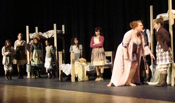 Brigid Harrington (center) as Annie, Caitlin Hughes as Miss Hannigan, and Emily Gulde Photo