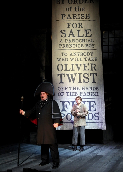 Eric Hoffmann as Mr. Bumble, a parish beadle and (rear) Quentin McCuiston as Oliver Twist