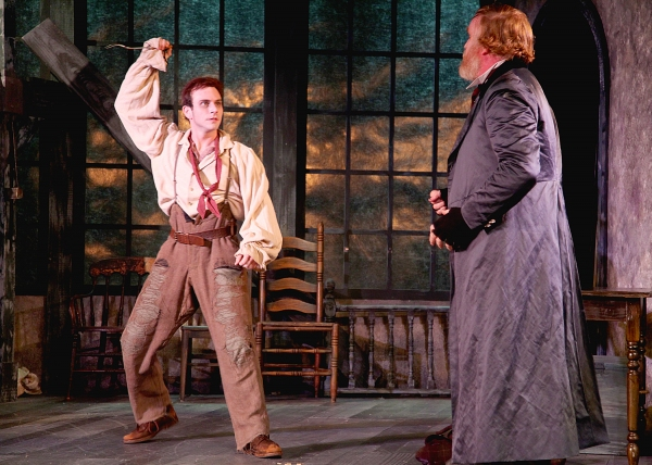 The Artful Dodger played by Robbie Collier Sublett threatens Fagin, the receiver of stolen goods played by Ames Adamson
