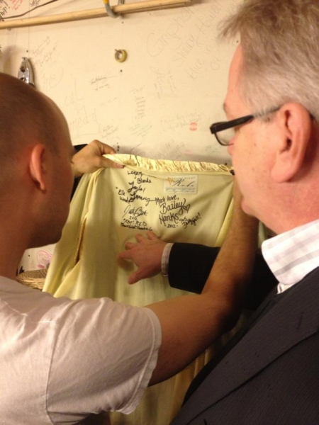 Paul Cook reads the autographs on the First Night Robe Photo