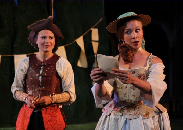 (front) Celia, played by Maria Tholl reads a letter from Orlando to the disguised Rosalind played by Caralyn Kozlowski.