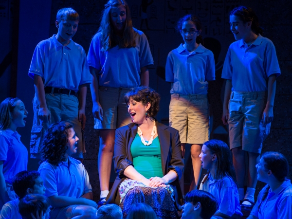 The Narrator, played by Laura Berger, surrounded by members of the children''s chorus. (Top Row: Tommy Cimato, Madison Cichon, Andrea Gameros, Jesse Pike. Bottom Row: India Chudnow, Alex Ohmart, McKenna Spanko, Josh Pike, Delaney Spanko, Nickela Rooney. C