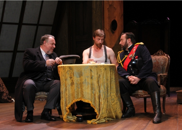 French banker Chauffourier-Dubieff played by Colin McPhillamy (left), and  Count Féodor Brekenski played by John Greenbaum (right) attempt to convince Prince Mikaïl Alexandrovitch Ouratieff played by Jon Barker (center) to give up his fortune.