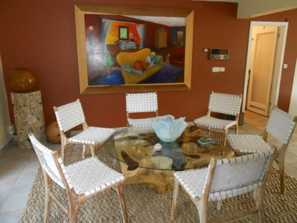 Dining area staged by Ernie J. Hulse beneath a painting by Scott Benjamin Tucker