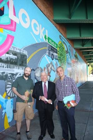 Brooklyn Borough President Marty Markowitz joins assistant artist Mark Evans (left) and lead artist Esteban Del Valle (right) at the unveiling of a new mural, painted with the help of student volunteers from Groundswell, which he helped unveil in the unde