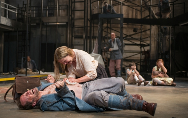 Beatriz (ensemble member Joan Allen, center) attempts to remove a bullet from a soldier (ensemble member Tim Hopper)