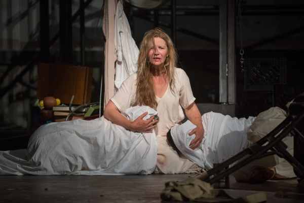 Beatriz (ensemble member Joan Allen) embraces two familiar dead bodies