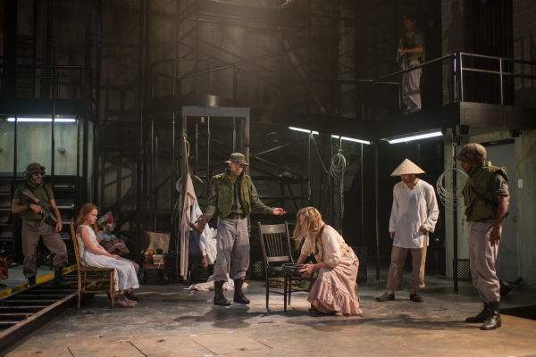 Glennister (ensemble member Tim Hopper, center) insists that Beatriz (ensemble member Joan Allen, center right) must prove that The Girl is miraculous as (left to right) a soldier (Kareem Bandealy), The Girl (Emma Gordon), The Boy (Daniel Pass), Xuan (Dem