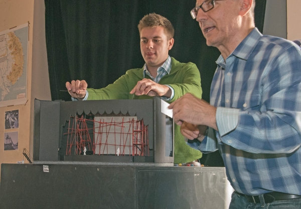 (from left)  Assistant Director Trent Stork helps Jim Corti, Artistic Director at the Paramount Theatre and director of Miss Saigon, shows his cast a model of Linda Buchanan's striking set design for the production.