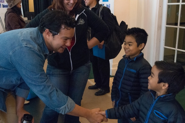Actor Peter Sipla shakes hands with eight-year-old Zachary Uzarraga on the first day of rehearsal.  Standing by is Zachary's older brother Matthew, Zachary's understudy in the role of Tam.