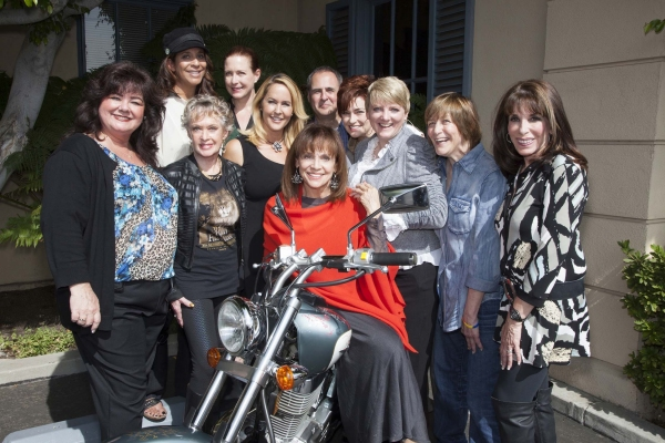 Tammy Locke, Christine Devine, Tippi Hedren, Katy Kurtzman, Erin Murphy, Valerie Harper, Grier Weeks, Carolyn Hennesy, Alison Arngrim, Geri Jewell and Kate Linder gather around Magaret Cho''s bike, signed for charity.