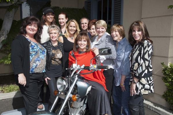 Tammy Locke, Christine Devine, Tippi Hedren, Katy Kurtzman, Erin Murphy, Valerie Harper, Grier Weeks, Carolyn Hennesy, Alison Arngrim, Geri Jewell and Kate Linder gather around Magaret Cho''s bike, signed for charity.