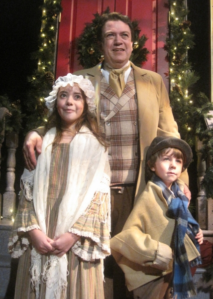 Real-life father of 11-year-old Sofia Murrell (Belinda Cratchit), left, and 6-year-old Sage Barber Murrell (Tiny Tim), right, Darrin Murrell (center, back) plays their stage father, Bob Cratchit