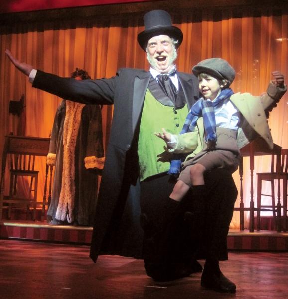 Ebenezer Scrooge (Jeff Stockberger) celebrates Christmas with Tiny Tim (6-year-old Sage Barber Murrell)