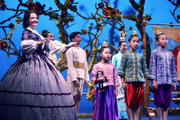 Michele Ragusa (as British schoolteacher Anna Leonowens), left, leads her pupils in song