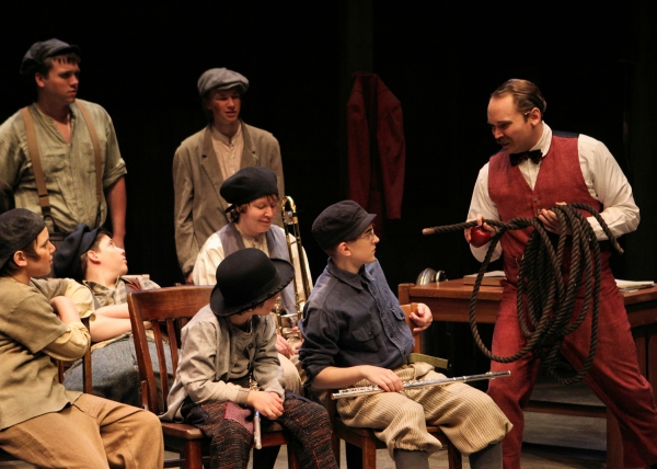 A.W. Warnock (Randy Schmeling) points out to the boys (l to r, front row: Jonah Harrison, Joshua Harrison, Izzy Karr; second row: Jack Alexander, Shelby Ernst; standing: Rory Mitchell, Chalres Couture) that ''all boys are working boys''