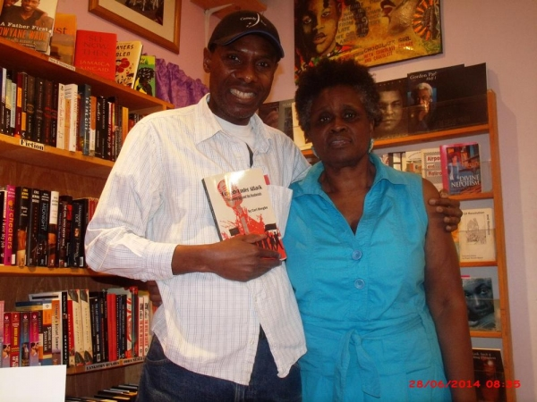 Author and Comedybeat.org managing editor Carl Unegbu greets Sisters Uptown Bookstore and Cultural Center owner Janifer Wilson