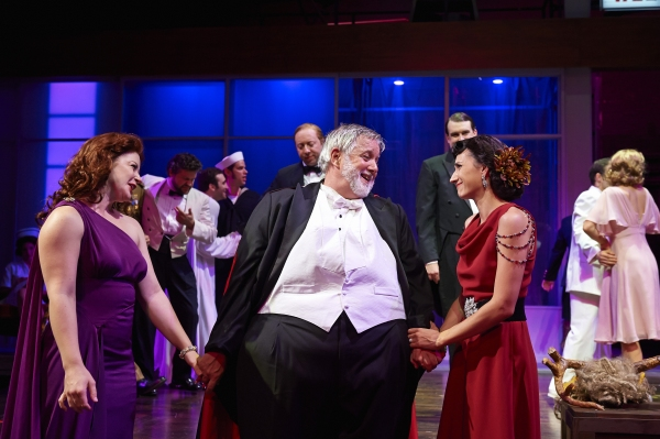 Actors Aled Davies (center, as Falstaff) shares the spotlight with the wise wives of Windsor, Laura Welsh Berg (right, as Mrs. Alice Ford) and Jodi Dominick (right as Mrs. Margaret Page)