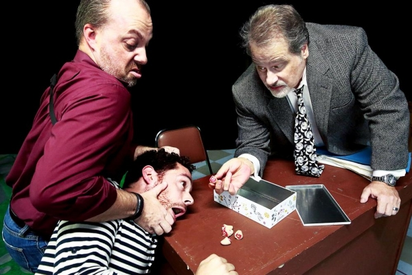 The detectives (Trevor B. Cone, Scott Holmes) show Katurian (Aaron Echegaray) the evi Photo