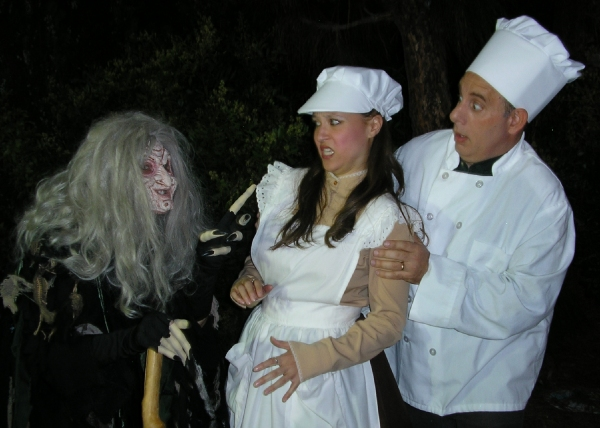 The Witch (Elizabeth Bouton) imposes her will upon the Baker (Terry Delegeane) and his Wife (Amy Coles).