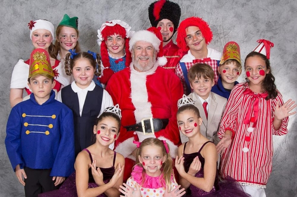 Santa is surrounded by toys: front row, from left, Julia Patella, Addison Blumberg and Jeanette Smith; middle row, from left, Dylan Katz, Maya Karp, Sheldon Bruce Zeff (as Santa), Teddy Brendel as Harry Finfer, Hudson Orfe and Makenna Katz; back row from