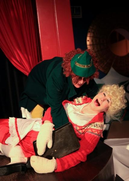 Elfina (Barbara Figgins) tries to help a drunken Ruth Claus (Ed Jones) off the floor