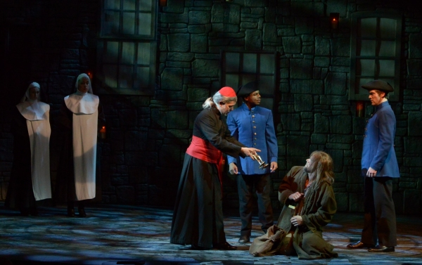 The Bishop (Gabriel Zenone) offers a gift to Valjean (Gregg Goodbrod), seated, as the constables (Cornelius Davis and Chris Crawford), right, and nuns (Emily Rynasko and Anna Kelly), left, look on