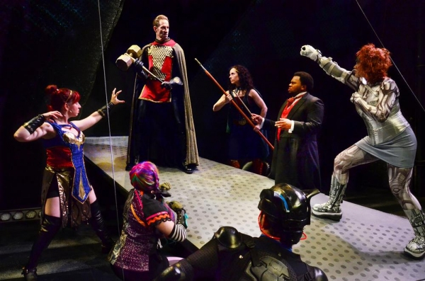 (clockwise from left) Corrbette Pasko as Damsel, Phil Timberlake as Dr. Impossible, Sarah Scanlon as Elphin, Frederick Harris as Mr. Mystic, Christina Hall As Fatale, Tommy Malouf as Blackwolf, and Taryn Wood as Rainbow Triumph