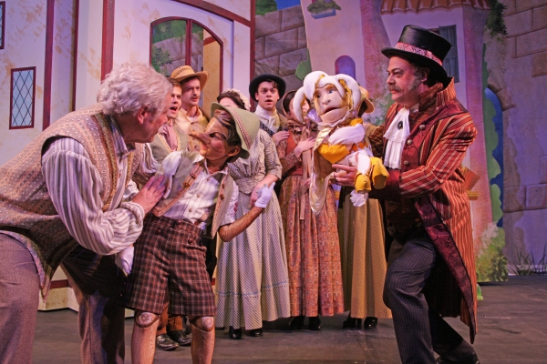 Geppetto (Nicholas F. Saverine) and Pinocchio (Topher Cundith) meet the puppeteer Stromboli (Shaun-Michael Morse).