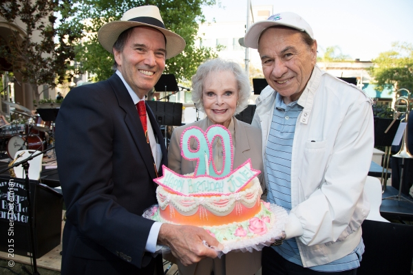 June Lockhart receives birthday cake from conductor Gary Greene (left), and two-time Oscar-winning composer Richard Sherman (right).