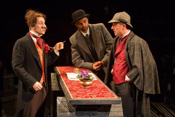 Blake Segal as Castilian Desk Clerk, Usman Ally as Doctor Watson, and Euan Morton as Sherlock Holmes
