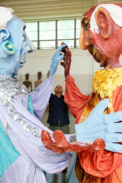 Kinan Valdez works with the Grandmother and Grandfather puppets Photo