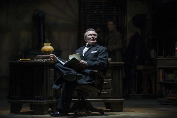 Jonathan Smoots as Ebenezer Scrooge and Jonathan Wainwright (background) as Bob Cratchit