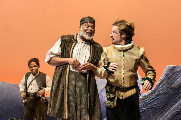 The Host of the Garter Inn (Raphael Nash Thompson) advises Doctor Caius (Jon Barker) as John Rugby (Felix Mayes) looks on