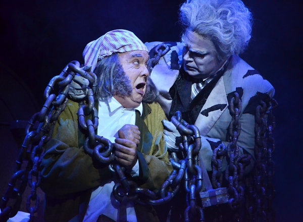 Ebenezer Scrooge (Eddie Curry), left, is horrified to learn that the fate that befell his business partner Jacob Marley (Daniel Klingler) could also be his own