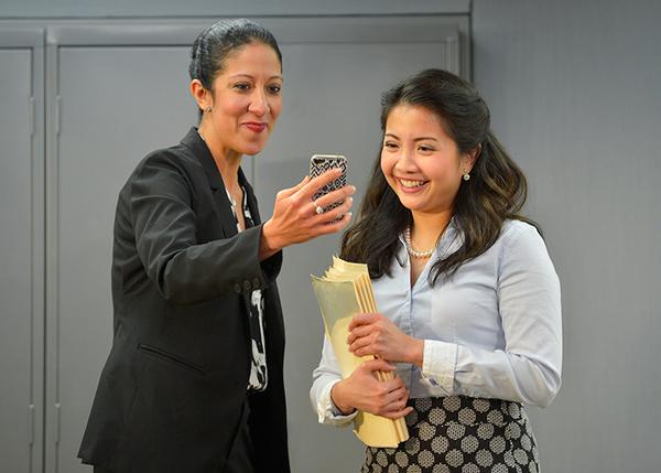 Charlene (Sarah Nina Hayon) and Vivan (Kristin Villanueva) in the break room, looking at pictures of Charlene's kids.