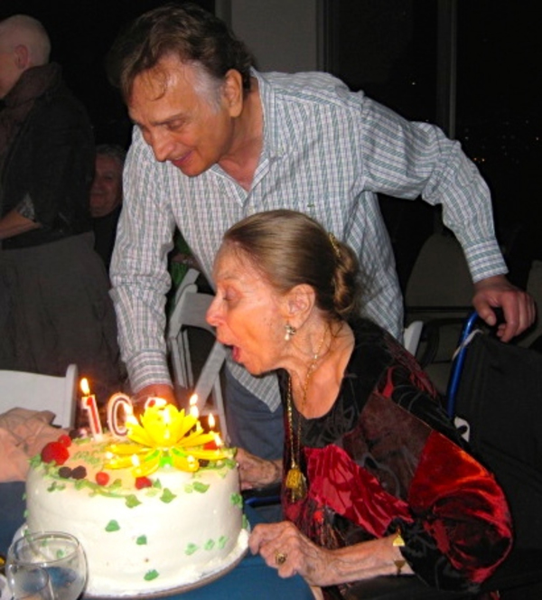 Party host, celebrated director John Bowab, stands by as Patricia Morison blows out her candles