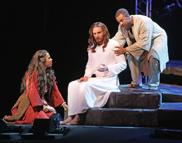 Mary Magdalene (Erin Clemons) sits at the feet of Jesus (Thaddeus Pearson) as Judas (Avery Smith) questions why Jesus would spend time with her. Photo Credit: Christopher Clark