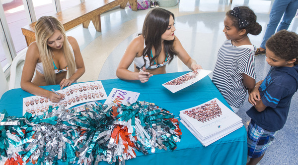 The Miami Dolphins Cheerleaders signing autographs for young visitors.