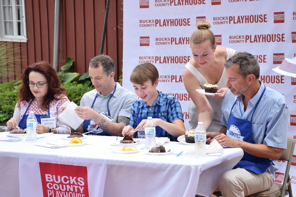 Abby Langsted, Bucks County Playhouse Marketing Manager (standing), brings cupcakes to be judged to the judges: (from left) Cast Members: Michele Ragusa, Euan Morton, Aidan J. Lawrence (14 years old) and Bucks County Playhouse Producing Director Alex Fras
