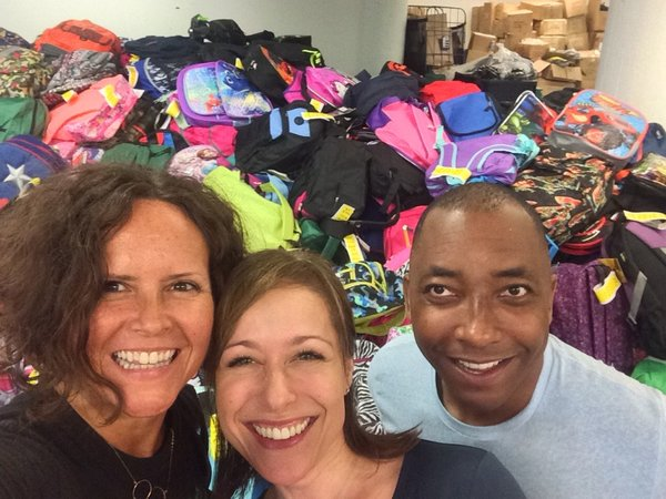 Volunteers persona; chef Lisa Adams, actress Paige Davis, and director/choreographer Christopher Windom help fill backpacks.