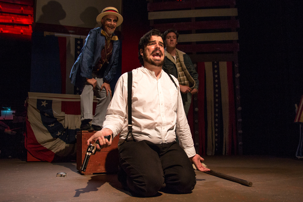 (L to R) Will Shupe as The Proprietor, Chris Kerrigan kneeling as John Wilkes Booth, Levi Gotsman as The Balladeer.
